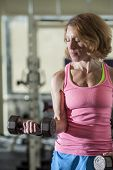 muscular middle age woman lifting weights