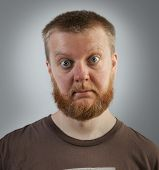 stock photo of bulge  - Bearded man with bulging eyes in a brown t - JPG