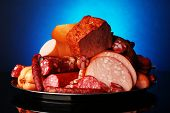 Lot of different sausages on salver on dark colorful background