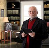 Portrait of elderly professor at study holding tablet computer