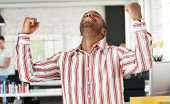 Casual black man celebrating success at office, arms raised.