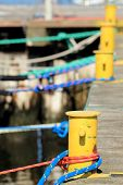 foto of bollard  - harbor quayside old yellow mooring bollard with blue red rope in marina - JPG