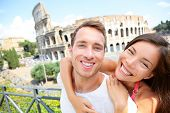 Happy travel couple in piggyback by Coliseum, Rome, Italy. Smiling young romantic couple in love tra