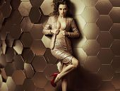Glamorous woman on wall of gold