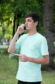 Attractive Young Guy Outdoors Calls By Telephone