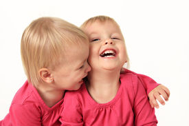 stock photo of identical twin girls  - Cute two year old identical twin girls laughing - JPG
