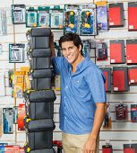 Portrait of happy young man with stacked toolboxes in hardware store