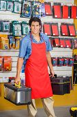 Portrait of smiling young salesman holding toolboxes in hardware shop