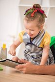 Closeup portrait of cute little girl with tablet cooking