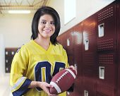 A beautiful teen girl happily holding a football in a locker room.