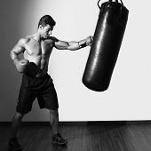 Full length of a shirtless muscular boxer with punching bag in gym