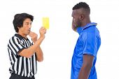 Referee showing yellow card to football player on white background