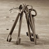 some old and rusty keys on a rustic wooden table, in sepia tone