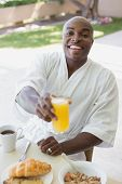 Handsome man in bathrobe having breakfast outside on a sunny day