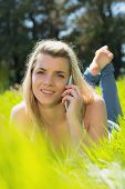 Pretty blonde lying on grass talking on phone smiling at camera on a sunny day in the countryside