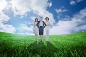Team of businesswomen looking at camera against green field under blue sky