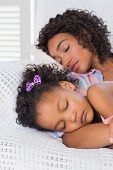 Cute daughter sleeping with mother on the sofa at home in the living room