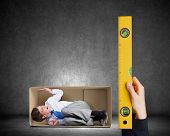 Close up of business person hand measuring man in carton box