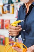 Cropped image senior man holding air compressor hose in hardware shop