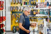 Side view of senior man working in hardware shop