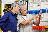 Senior male customer examining packed screwdriver while vendor looking at it in hardware shop