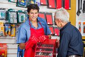 Portrait of smiling young salesman showing drill bit to senior man in hardware store