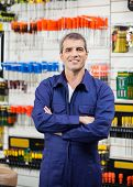 Portrait of smiling worker with arms crossed in hardware store