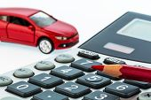 a car and a red pen is on a calculator. cost of gasoline, wear and insurance. car costs are not paid
