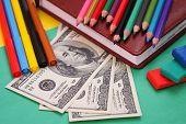 Pens, colored pencils, plasticine, book, hundred dollar bills