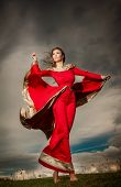 Fashionable beautiful young woman in red long dress posing outdoor with cloudy dramatic sky