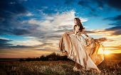 Fashionable beautiful young woman in nude colored long dress leaving, cloudy dramatic sky