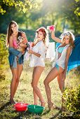 Three sexy women with provocative outfits putting clothes to dry in sun. Sensual young females