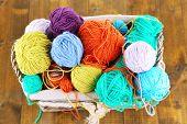 Multicoloured knitting yarn in basket on wooden background