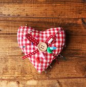 Fabric heart with color pins and safety pins on wooden background