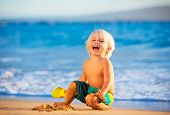 Happy young boy playing at the beach