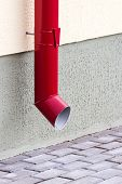 stock photo of downspouts  - Wall of house with red metall downspout and pavement - JPG