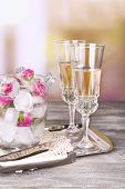 Ice cubes with rose flowers in glass bucket and two glasses with champagne on wooden table, on brigh