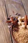 Brown sugar cubes, reed and crystal sugar in bowl on wooden background