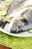 Two fish dorado with lemon on plate on wooden table close-up