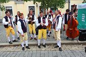 DOMAZLICE CZECH REPUBLIC - AUGUST 9, 2014: Unidentified street musicians dressed in traditional Czech (Pilsen) garb dancing and singing on The Chodske slavnosti medieval market.
