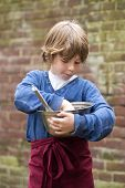Boy with a sweet tooth, muncing the left overs from batter  in a bowl he's holding