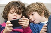Cute boy looking at his younger sister who is playing a game on a smart phone on sofa
