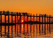 Tourist crossing on bridge over lake during sunset at Mandalay, Myanmar, silhouette
