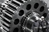 machine engineers, workers with giant cogs and gears in the background
