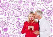 Handsome man giving his wife a kiss on cheek against heart pattern