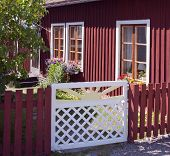 Red wooden building with a white gate.