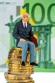 pensioners sitting on money stack symbol photo for pension, retirement, old age