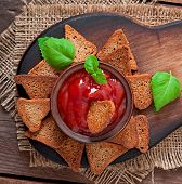 Rye rusks with spicy sauce on a wooden background