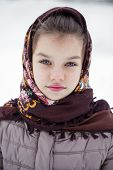 Close-up portrait of a little girl in brown jacket and knit scarf and hat on a background of a snow park