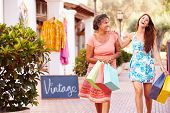 Mother With Adult Daughter On Street Carrying Shopping Bags